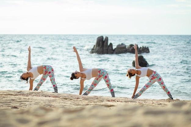 Tre donna che giocano posa yoga sulla spiaggia del mare