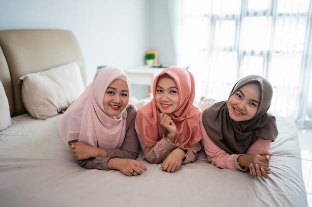 Tre donna musulmana sdraiata e piace chiacchierare sul letto