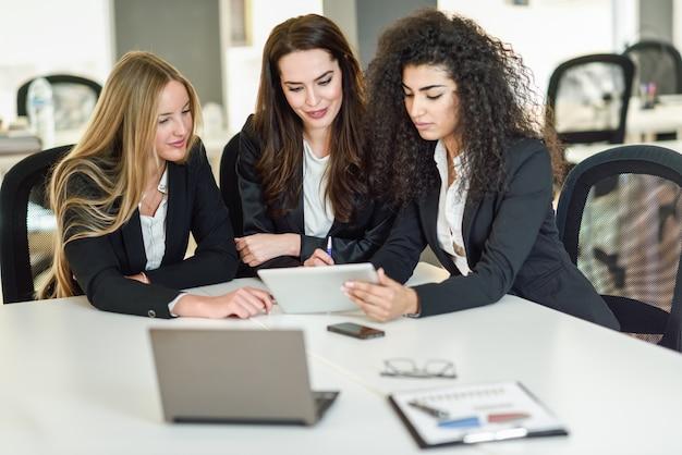Tre donne d'affari che lavorano insieme in un ufficio moderno