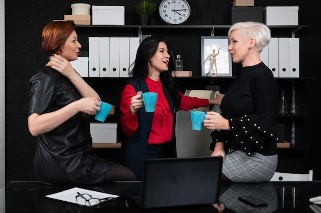 Tre donne d'affari, parlando con il caffè in mano in ufficio elegante