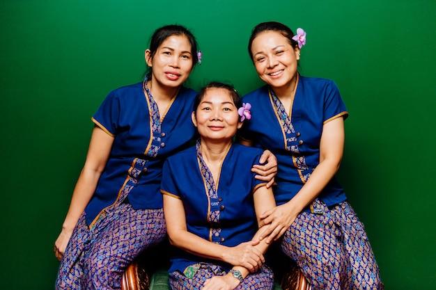 Tre donne del personale dell'hotel di massaggiatori etnici, felici e sorridenti tailandesi con il fiore dell'orchidea in ritratto dei capelli in costumi tradizionali esotici orientali della stazione termale che esaminano macchina fotografica