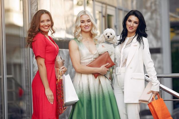 Tre donne eleganti con borse della spesa in una città