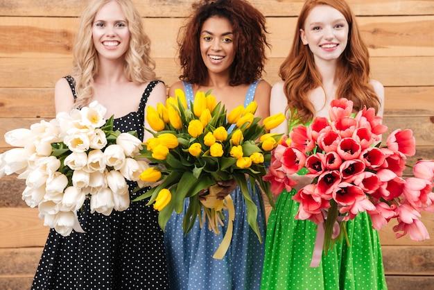 Tre donne felici che tengono i mazzi di fiori