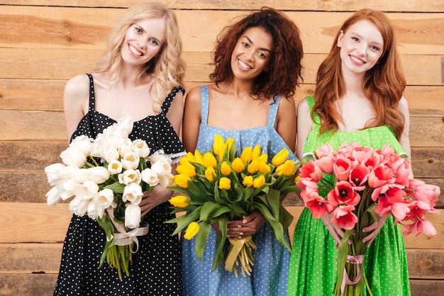 Tre donne graziose che tengono i mazzi di fiori