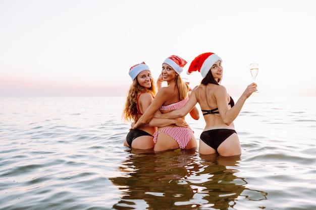 Tre donne in cappelli di babbo natale si divertono sulla spiaggia del mare o dell'oceano al tramonto.