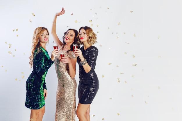 Tre donne in festa in abito da sera scintillante che si godono del tempo insieme, bevono vino e ballano