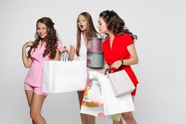Tre donne in posa emotivamente in grigio dopo lo shopping con molti sacchi di carta e regali.