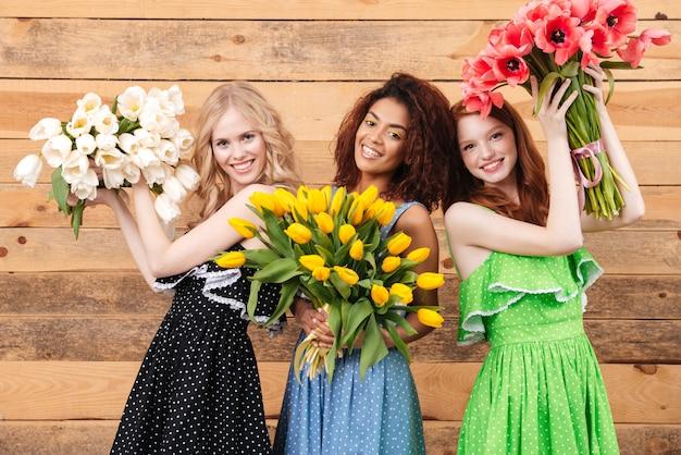 Tre donne soddisfatte che tengono mazzi di fiori