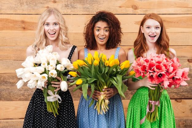 Tre donne sorprese che tengono i mazzi di fiori