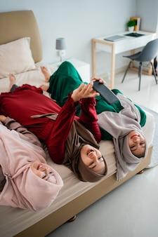 Tre donne velate si sdraiano e le mani sollevate sul letto mentre fanno un selfie insieme