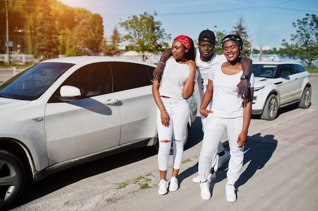 Tre eleganti amici afroamericani, indossano abiti bianchi contro due auto di lusso. la moda di strada dei giovani neri. uomo di colore con due ragazze africane.