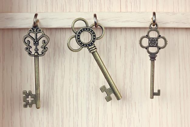 Tre figure chiave in metallo color oro appese ai ganci.