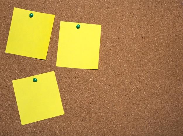 Tre fogli di appunti sono appuntati sulla bacheca di sughero per la scrittura
