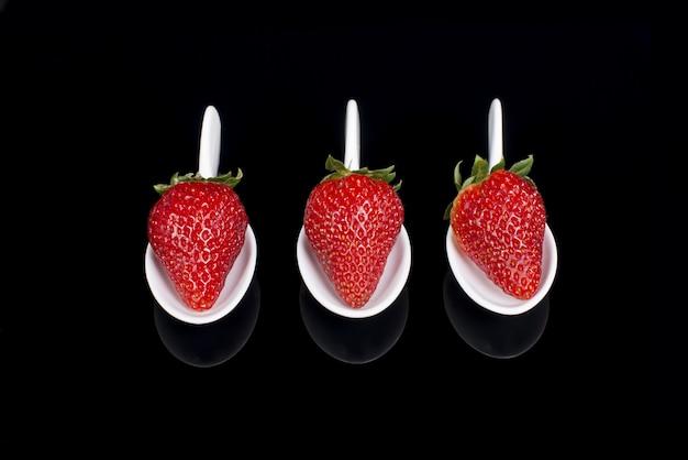 Tre fragole in cucchiai di maiolica