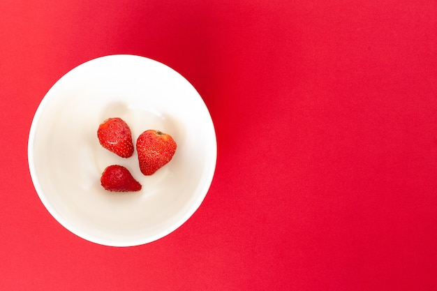 Tre fragole rosse su un piatto bianco, isolato.