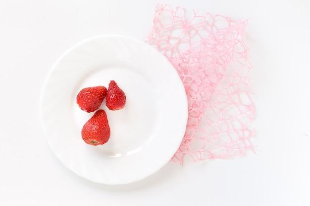Tre fragole rosse su un piatto bianco sulla maglia rosa della decorazione