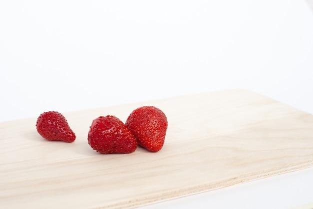 Tre fragole rosse sul tagliere di legno marrone chiaro della cucina