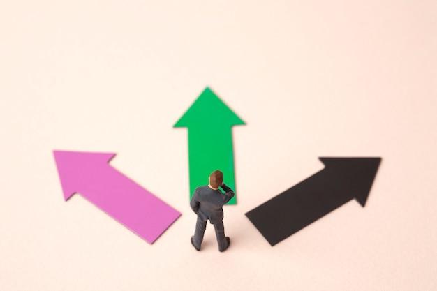 Tre frecce di direzione con un uomo d'affari in miniatura