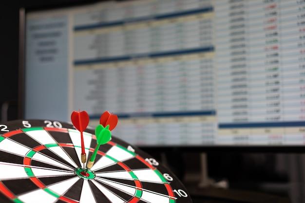 Tre freccette colpiscono il bersaglio sullo sfondo delle statistiche di scambio sullo schermo del monitor