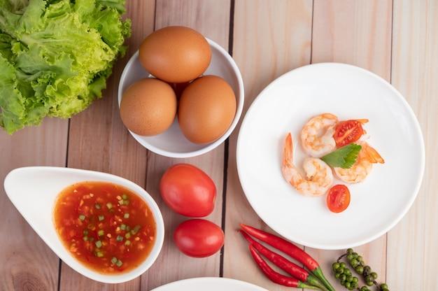 Tre gamberi freschi, uova, peperoncino, salsa e mezzo pomodori in un piatto bianco su un legno.