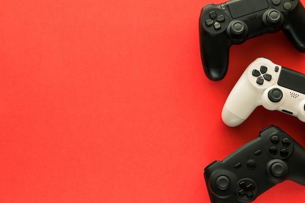 Tre gamepad su un tavolo rosso e copia spazio