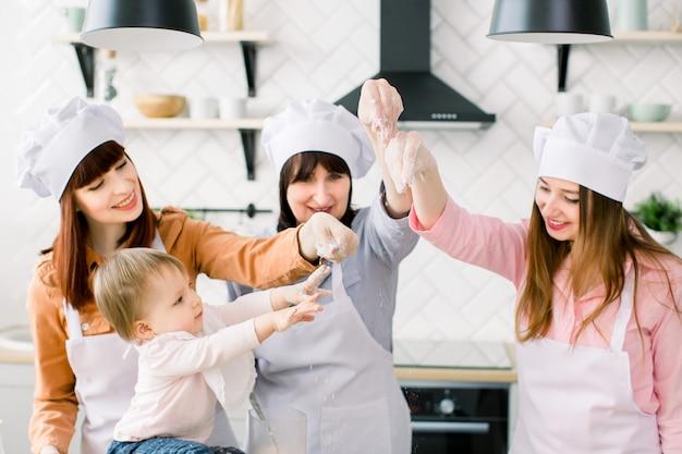Tre generazioni di donne in grembiule bianco stanno preparando la pasta per la pizza in cucina per la festa della mamma
