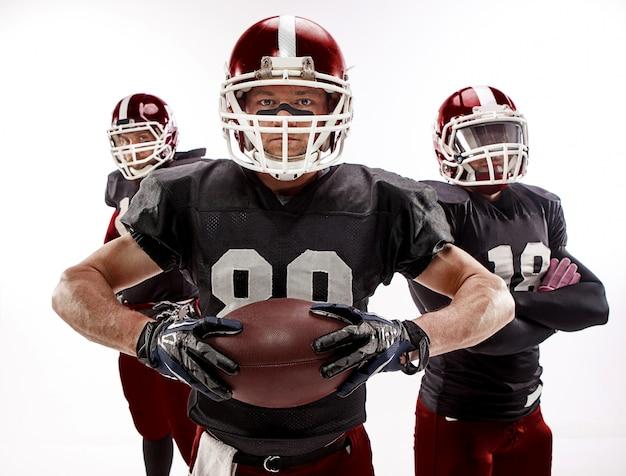 Tre giocatori di football americano in posa con la palla su bianco