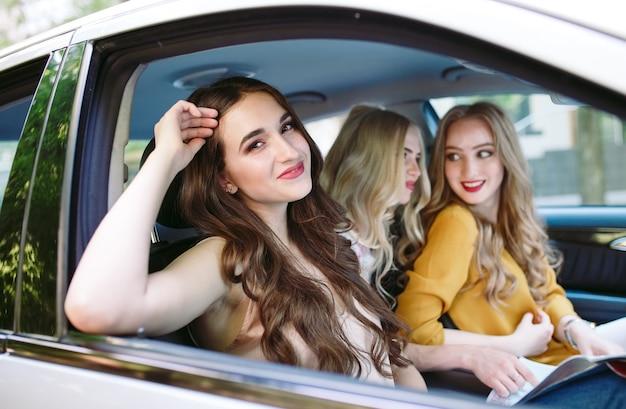 Tre giovani amiche che viaggiano in macchina