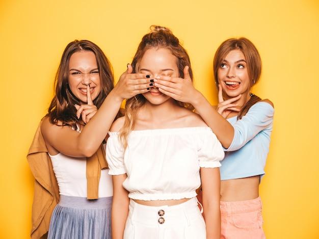 Tre giovani belle ragazze sorridenti dei pantaloni a vita bassa in vestiti d'avanguardia di estate donne spensierate sexy che posano vicino alla parete gialla. le modelle positive sorprendono la sua migliore amica, le coprono gli occhi e hu