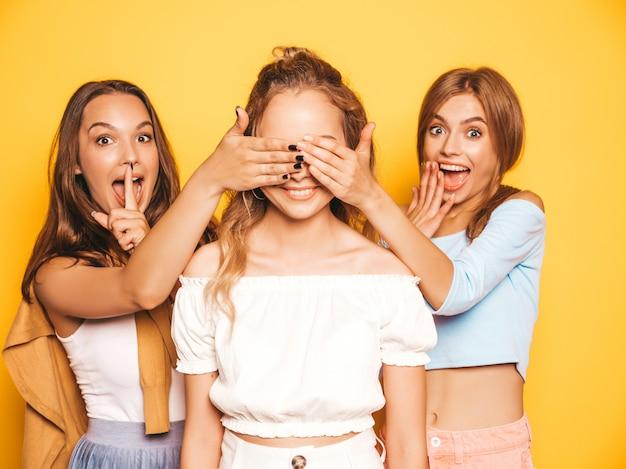 Tre giovani belle ragazze sorridenti dei pantaloni a vita bassa in vestiti estivi d'avanguardia donne spensierate sexy che posano vicino alla parete gialla modelli che sorprendono il loro amico coprono gli occhi e abbracciano da dietro