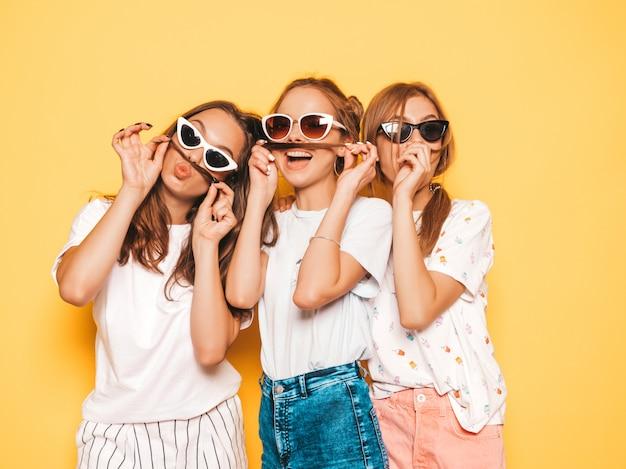 Tre giovani belle ragazze sorridenti hipster in abiti estivi alla moda. donne spensierate sexy che posano vicino alla parete gialla. modelle positive che impazziscono e si divertono. fare baffi con i capelli