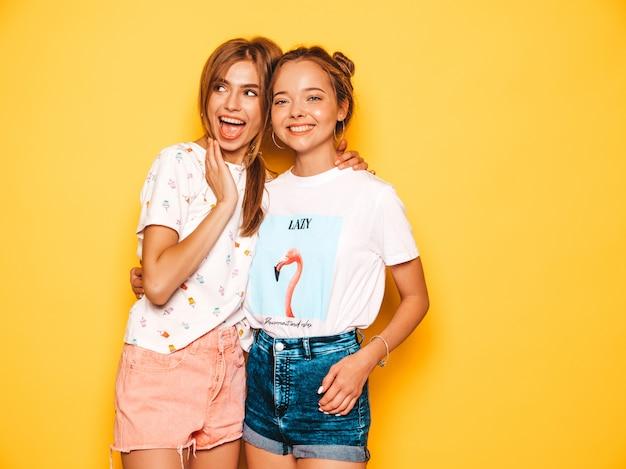 Tre giovani belle ragazze sorridenti hipster in abiti estivi alla moda. donne spensierate sexy che posano vicino alla parete gialla. modelle positive che impazziscono e si divertono. in occhiali da sole