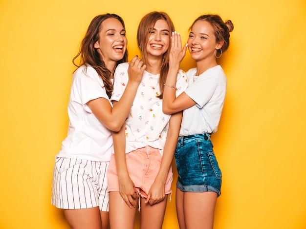 Tre giovani belle ragazze sorridenti hipster in abiti estivi alla moda. donne spensierate sexy che posano vicino alla parete gialla. modelle positive che impazziscono e si divertono