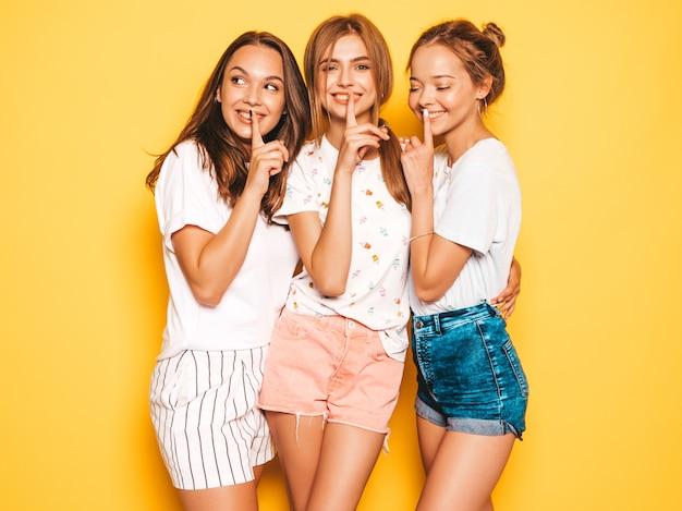 Tre giovani belle ragazze sorridenti hipster in abiti estivi alla moda. donne spensierate sexy che posano vicino alla parete gialla modelli positivi che impazziscono mostrando il segno di silenzio del dito di silenzio, gesto
