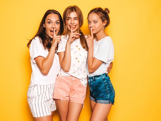 Tre giovani belle ragazze sorridenti hipster in abiti estivi alla moda. donne spensierate sexy che posano vicino alla parete gialla. modelli positivi che mostrano il segno di silenzio del dito del silenzio, gesto