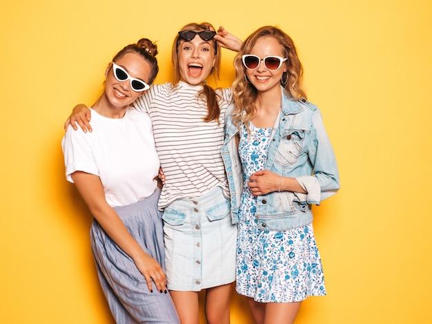 Tre giovani belle ragazze sorridenti hipster in abiti estivi alla moda. donne spensierate sexy che posano vicino alla parete gialla. modelli positivi che si divertono in occhiali da sole