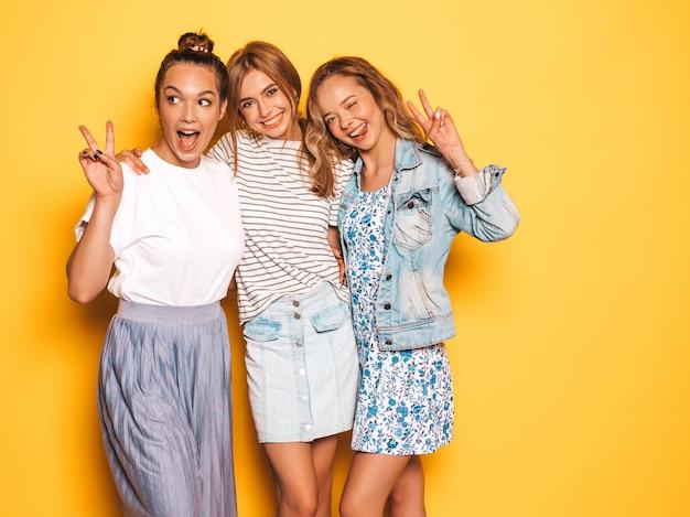 Tre giovani belle ragazze sorridenti hipster in abiti estivi alla moda. donne spensierate sexy che posano vicino alla parete gialla. modelli positivi che si divertono. mostrano il segno di pace