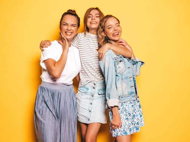 Tre giovani belle ragazze sorridenti hipster in abiti estivi alla moda. donne spensierate sexy che posano vicino alla parete gialla. modelli positivi che si divertono