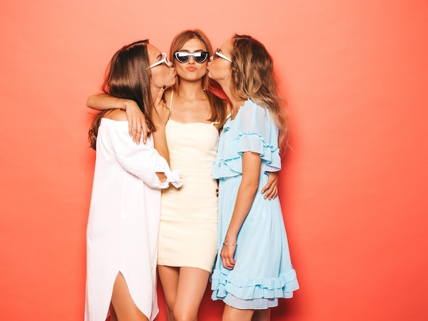 Tre giovani belle ragazze sorridenti hipster in abiti estivi alla moda. donne spensierate sexy che posano vicino alla parete rosa. modelle positive che impazziscono e si divertono. bere il loro amico sulla guancia