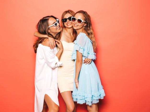 Tre giovani belle ragazze sorridenti hipster in abiti estivi alla moda. donne spensierate sexy che posano vicino alla parete rosa. modelle positive che impazziscono e si divertono con gli occhiali da sole