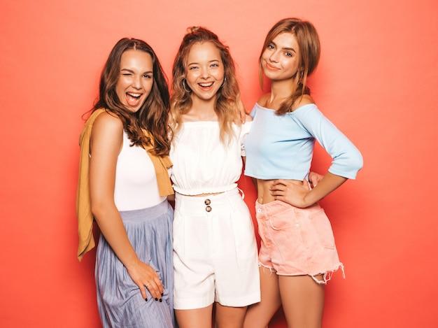 Tre giovani belle ragazze sorridenti hipster in abiti estivi alla moda. donne spensierate sexy che posano vicino alla parete rosa. modelli positivi che si divertono