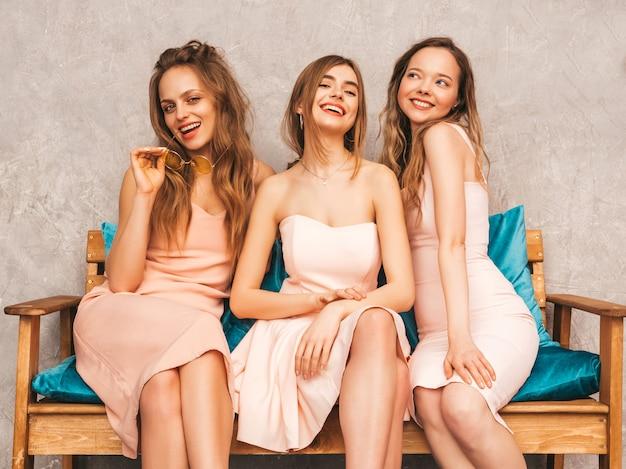 Tre giovani belle ragazze sorridenti in abiti alla moda estate rosa. donne spensierate sexy che si siedono sul sofà nell'interno di lusso. modelli positivi che si divertono e comunicano