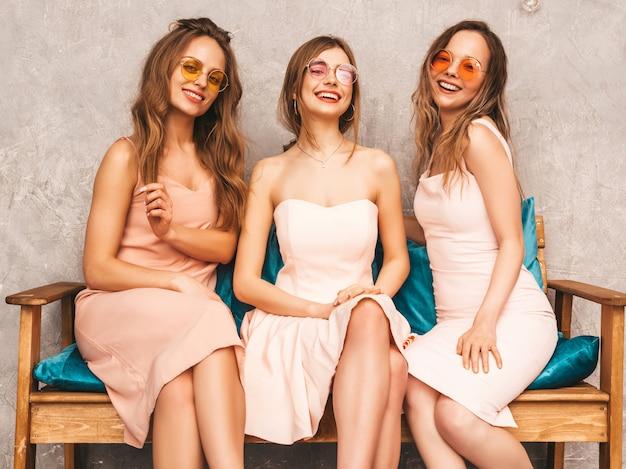 Tre giovani belle ragazze sorridenti in abiti alla moda estate rosa. donne spensierate sexy che si siedono sul sofà nell'interno di lusso. modelli positivi in occhiali da sole rotondi che si divertono e comunicano