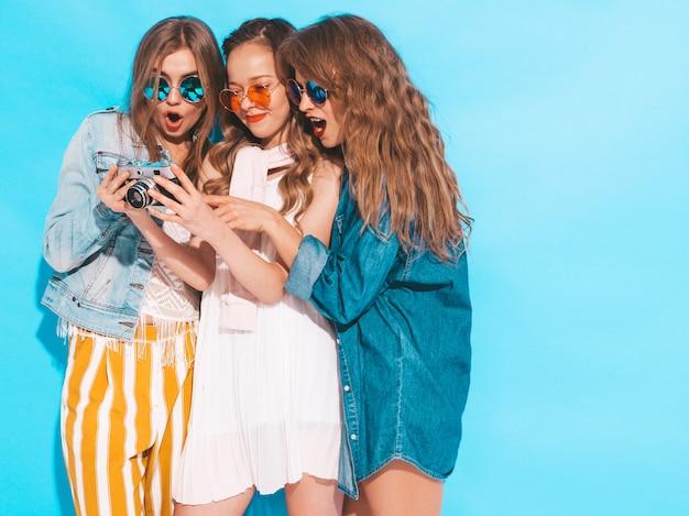 Tre giovani belle ragazze sorridenti in abiti casual e occhiali da sole alla moda estate. posa sexy spensierata delle donne. guardando le foto fatte sulla fotocamera retrò