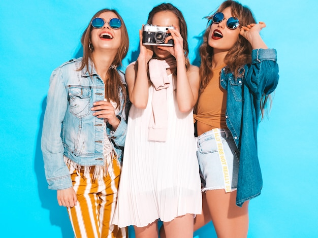 Tre giovani belle ragazze sorridenti in abiti casual e occhiali da sole alla moda estate. posa sexy spensierata delle donne. scattare foto con fotocamera retrò