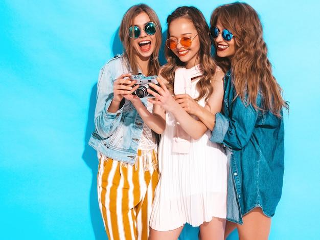 Tre giovani belle ragazze sorridenti in abiti casual estivi alla moda e in occhiali da sole. posa sexy spensierata delle donne. scattare foto con fotocamera retrò