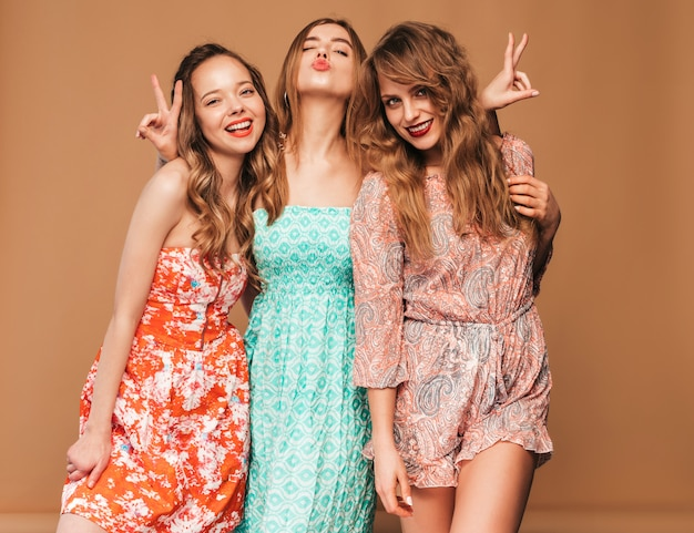 Tre giovani belle ragazze sorridenti in abiti casual estivi alla moda e in occhiali da sole. posa sexy spensierata delle donne.