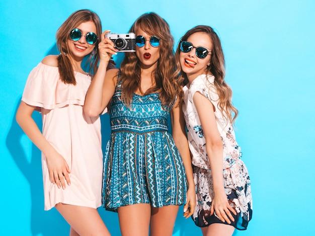 Tre giovani belle ragazze sorridenti in abiti casual estivi alla moda. posa sexy spensierata delle donne. scattare foto con fotocamera retrò