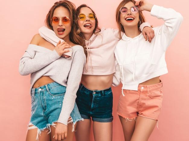 Tre giovani belle ragazze sorridenti in abiti estivi alla moda. posa sexy spensierata delle donne. modelli positivi che si divertono. abbracciare e mostrare la lingua