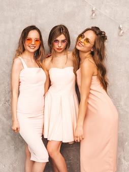 Tre giovani belle ragazze sorridenti in abiti rosa chiaro alla moda estate. posa sexy spensierata delle donne. modelli positivi in occhiali da sole rotondi che si divertono